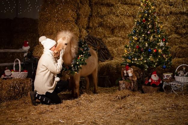 Ozdoby świąteczne na stajniach. piękny kucyk z wieńcem na szyi. choinka z balonami, strefa zdjęć na nowy rok. starsza kobieta całuje konia