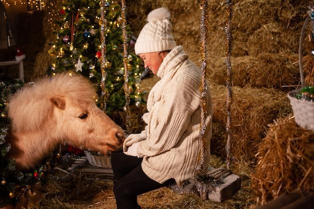 Ozdoby świąteczne na stajniach. piękny kucyk z wieńcem na szyi. choinka z balonami, strefa zdjęć na nowy rok. starsza kobieta i koń