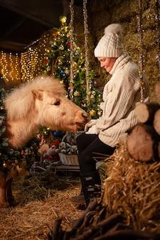 Ozdoby świąteczne na stajniach. piękny kucyk z wieńcem na szyi. choinka z balonami, strefa zdjęć na nowy rok. starsza kobieta siedzi na huśtawce karmiąc kucyka