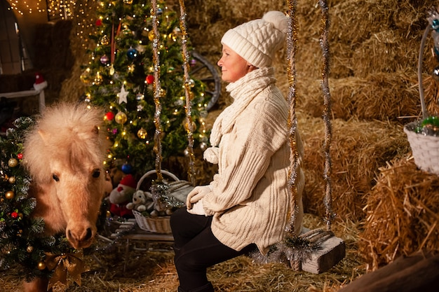 Ozdoby świąteczne na stajniach. piękny kucyk z wieńcem na szyi. choinka z balonami, strefa zdjęć na nowy rok. starsza kobieta