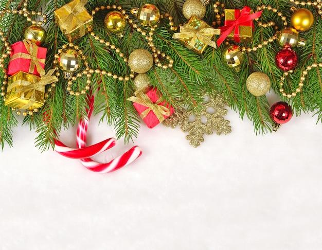 Ozdoby świąteczne na świerkowej gałęzi na białym tle