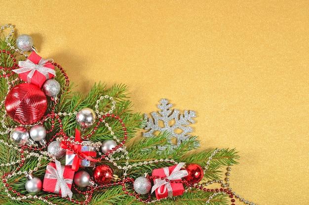 Ozdoby świąteczne na świerkowej gałęzi na złotym tle