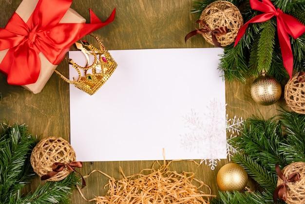 Ozdoby świąteczne na zielonym drewnianym teksturowanym tle, widok z góry, wolne miejsce na projekt, biała kartka papieru z kolorowymi kredkami i korona