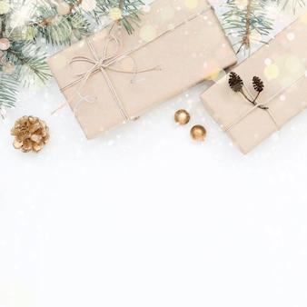 Ozdoby świąteczne, pudełka na prezenty, gałązki na śnieżnym białym tle.