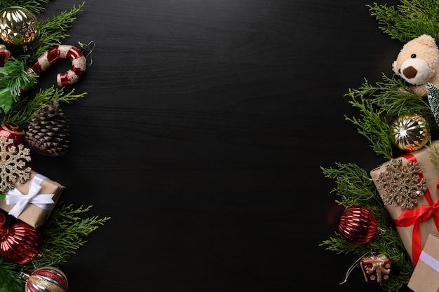 Ozdoby świąteczne, pudełka na prezenty, szyszka, misia i gałęzie jodły ozdoba na ciemnym tle.