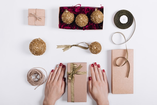 Ozdoby świąteczne, pudełka z prezentami i ręce kobiet