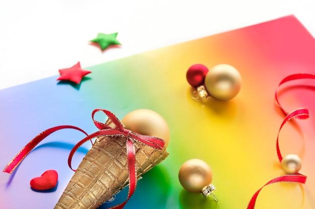 Ozdoby świąteczne w kolorach tęczowej flagi społeczności lgbtq, rożek waflowy do lodów, metalowe kulki, gwiazdki i kształt serca na papierze tęczowym, symbol dumy lgbt