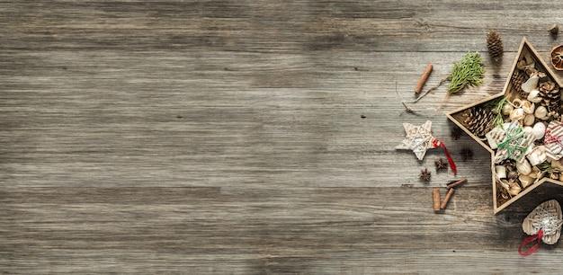 Ozdoby świąteczne w pudełku w kształcie gwiazdy na starym drewnianym tle