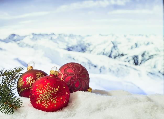 Ozdoby świąteczne w zaspie przed zaśnieżonymi górami zima boże narodzenie powierzchnia