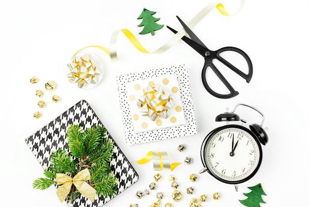 Ozdoby świąteczne z budzikiem i prezentami w kolorach złota na białym tle z pustą kopią miejsca na tekst. wakacje i uroczystości. płaski układanie, widok z góry