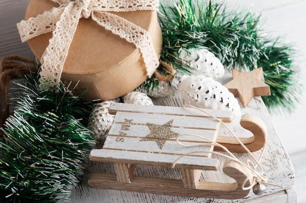 Ozdoby świąteczne z drewnianymi saniami i pudełkiem upominkowym z papieru kraft. noworoczny wystrój z zabawkami w stylu rustykalnym