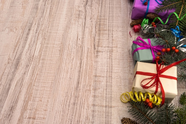 Ozdoby świąteczne z gałęzi jodły na drewnianym stole. pudełka na prezenty ze wstążkami. przedstawia koncepcję