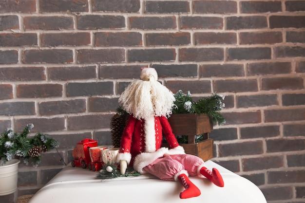 Ozdoby świąteczne, zabawkowy mikołaj z białą brodą siedzi na tle brązowego muru.
