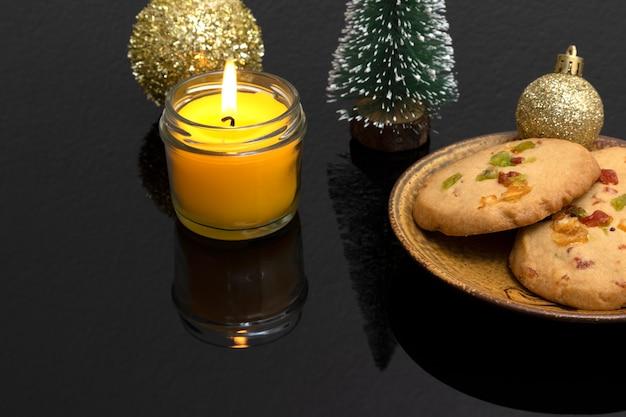 Ozdoby świątecznego stołu z ciasteczkami ze skórki pomarańczy, miniaturową sosną i świeczką zapachową.