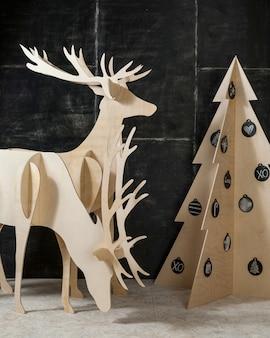 Ozdoby sylwestrowe i bożonarodzeniowe oraz sklejka jodłowa jelonek i drzewo na ciemnym tle