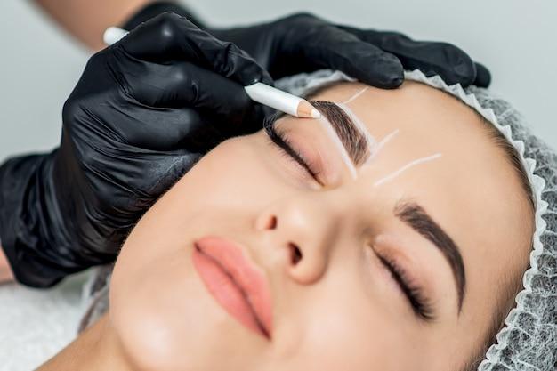 Oznaczenie białą kredką na brwiach młodej kobiety do zabiegu makijażu permanentnego