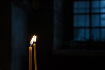 Płonące świece woskowe przy oknie w ciemnym pokoju