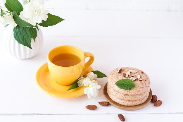 Pachnąca herbata jaśminowa w filiżance z migdałowymi ciasteczkami na śniadanie. białe drewniane tło.