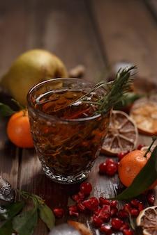Pachnąca herbata owocowa z mandarynkami, suszonymi cytrynami i rozmarynem na drewnianym stole. stylu country.