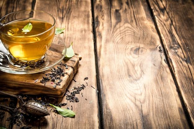 Pachnąca herbata z łyżeczką zaparzacza na drewnianym stole.