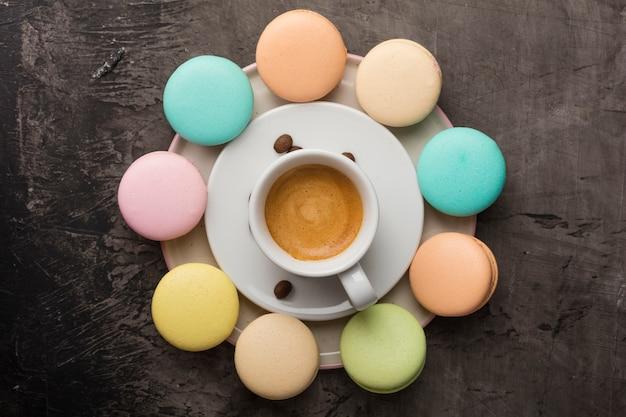 Pachnąca kawa i kolorowe ciasteczka macaron ułożone są w okrąg na talerzu