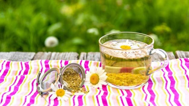 Pachnąca poranna herbata na świeżym powietrzu z dodatkiem płatków rumianku.