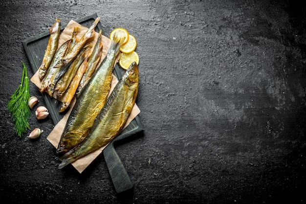Pachnąca wędzona ryba z ziołami, plasterkami czosnku i cytryną. na czarnym rustykalnym