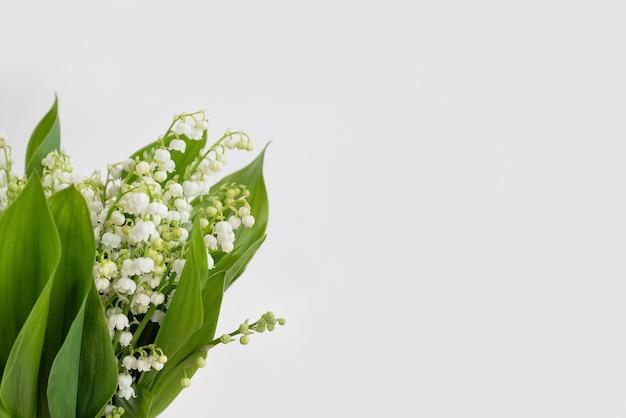 Pachnąca wiązka kwiatów konwalii na białej powierzchni ściany