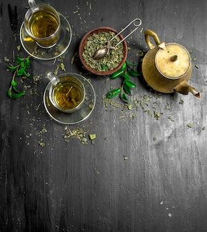 Pachnąca zielona herbata w szklanych filiżankach na czarnej tablicy