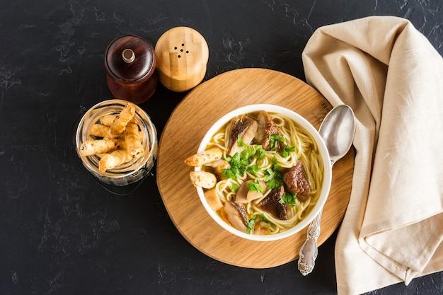 Pachnąca zupa z białych grzybów w misce na okrągłym drewnianym stojaku. widok z góry. czarne tło.