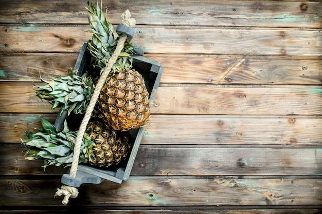 Pachnące ananasy w pudełku. na drewnianym