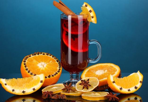 Pachnące grzane wino w szklance z przyprawami i pomarańczami dookoła na niebieskim tle