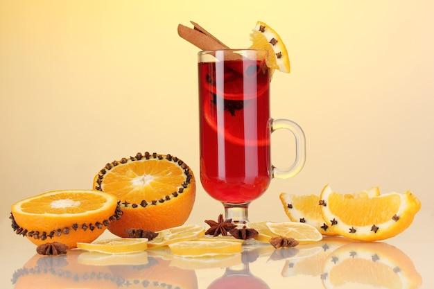 Pachnące grzane wino w szklance z przyprawami i pomarańczami dookoła na żółtym tle
