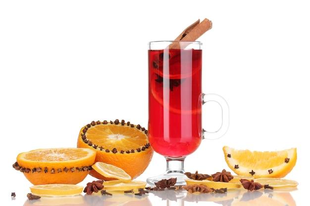 Pachnące grzane wino w szklance z przyprawami i pomarańczami wokół na białym tle