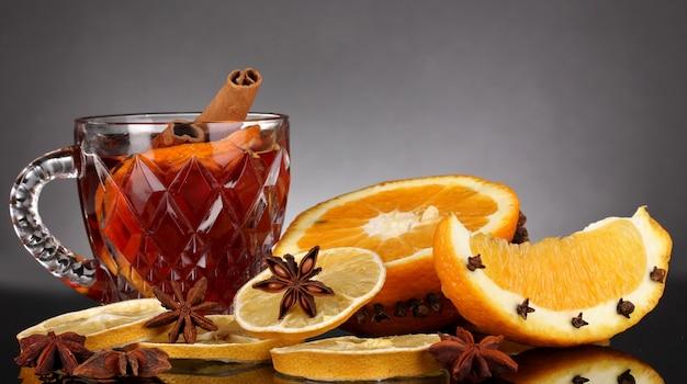 Pachnące grzane wino w szklance z przyprawami i pomarańczami wokół na czarnym tle