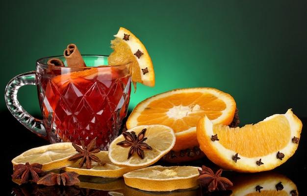 Pachnące grzane wino w szklance z przyprawami i pomarańczami wokół na zielonym tle