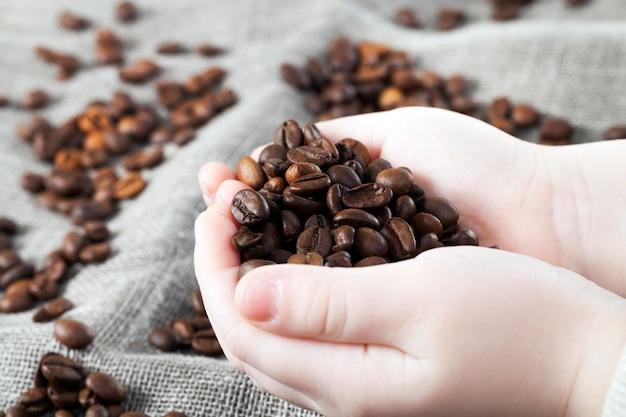 Pachnące ziarna kawy leżące na szarym materiale lnu