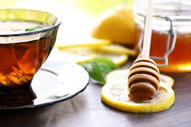 Pachnący świeży miód z filiżanką czarnej herbaty