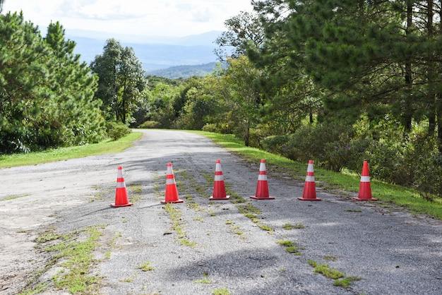 Pachołek drogowy - pomarańczowe pachołki drogowe stojące w rzędzie na asfalcie na górskiej drodze