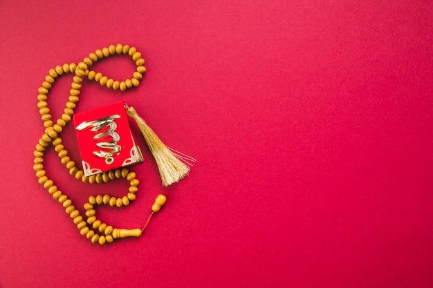 Paciorki różańca z małym koranem na stole