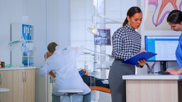 Pacjenci proszący o pomoc w wypełnieniu formularza rejestracji stomatologicznej przygotowującej się do badania. starsza kobieta siedzi na krześle w poczekalni zatłoczonego gabinetu ortodonty, podczas gdy lekarz pracuje w tle