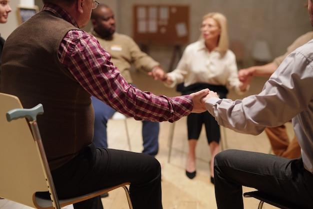 Pacjenci psychologa trzymający się za ręce podczas omawiania problemów na sesji