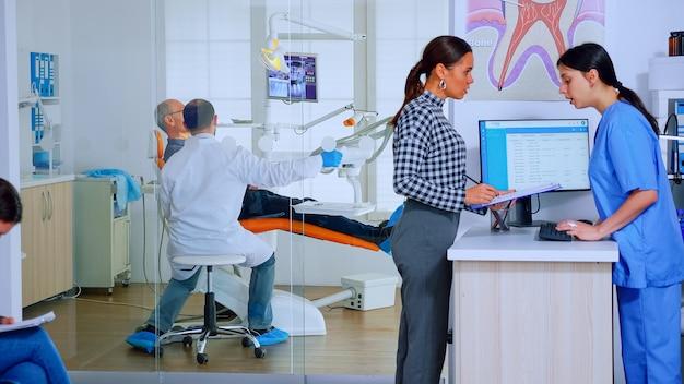 Pacjenci pytający o informacje wypełniający dokument stomatologiczny przygotowujący do badania zębów. starsza kobieta siedzi na krześle w poczekalni zatłoczonego gabinetu ortodonty, podczas gdy lekarz pracuje w tle