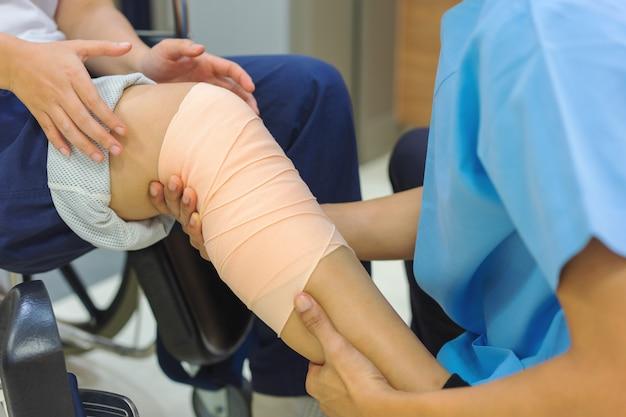 Pacjenci siedzący na wózku inwalidzkim mają ból w kolanie, który jest zabandażowany.