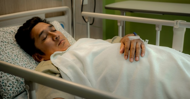 Pacjenci trzymają rękę z kaniulą na łóżku na oddziale