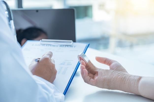 Pacjenci w wypadku ręki, lekarze zgłaszają wyniki badań lekarskich i zalecają leki.