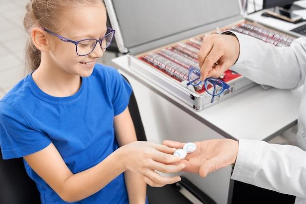 Pacjent bierze pojemnik z soczewkami kontaktowymi od lekarza.
