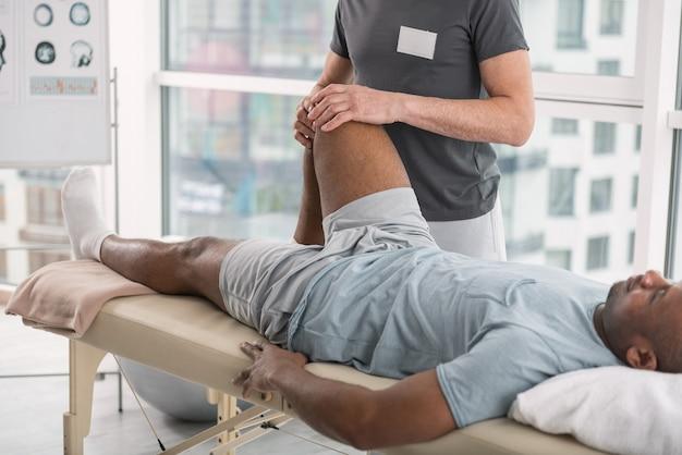 Pacjent centrum rehabilitacji. miły młody człowiek leżący na kanapie lekarskiej, radzący sobie z konsekwencjami traumy