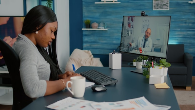 Pacjent chory student omawiający objawy choroby z lekarzem podczas konsultacji telezdrowotnej przez wideorozmowę, siedząc przy biurku w salonie