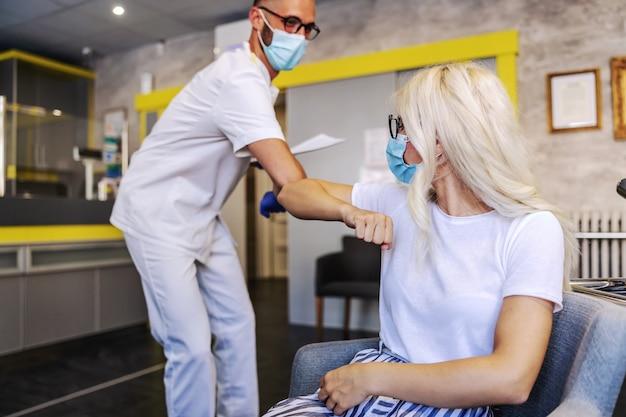 Pacjent i lekarz witają się łokciami